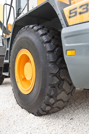 Black wheel with yellow disk of front loader on white stone road Reklamní fotografie