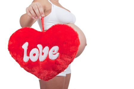 Pregnant woman hold red hart with love in hands on white background