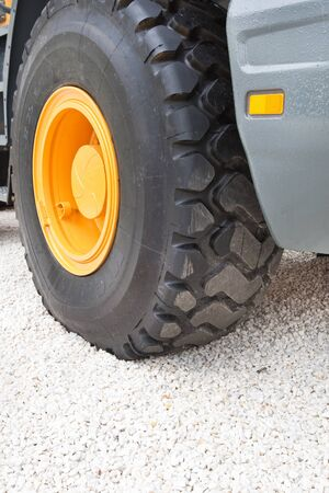 front end: Black wheel with yellow disk of front loader on white stone road Stock Photo