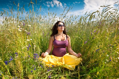 Pregnant woman on green grass field under blue sky in summer