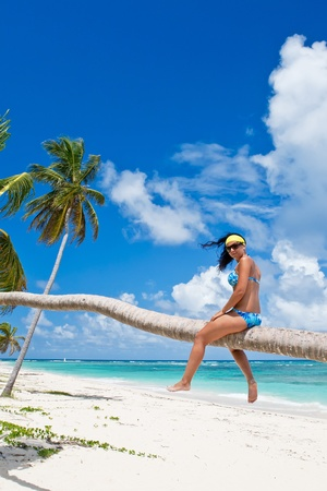 Tanned woman sitting on a palm white sand beach near ocean photo