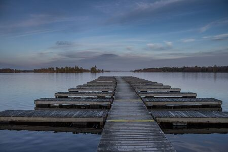 A spring scene of an empty dock, before the boating season begins with a beautiful sunset in the background