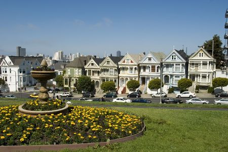 Alamos Square Seven Sisters one of the most famous views in San Francisco California with fountain and Yellow Flowers Stock Photo
