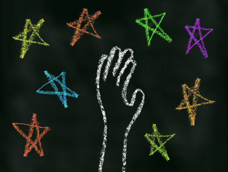 unreachable: Hand reaching for the stars illustration on blackboard Stock Photo