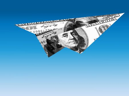 Paper plane made from folded one hundred dollar bill on flight. Stock Photo