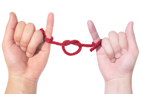 couple hand tied with a red string