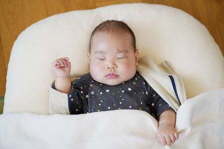 A Japanese baby sleeping in the living room.