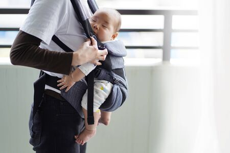 A mother and her five-month-old baby on a walk by baby carrier