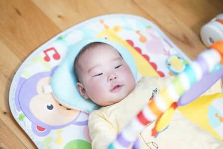 A 5-month-old japanese baby playing in the baby gym