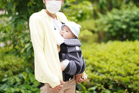 A mother and her five-month-old baby on a walk by baby carrier. A mother wearing a mask to prevent infection.
