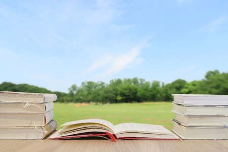 A book on a wooden desk - background image of fresh green and blue sky