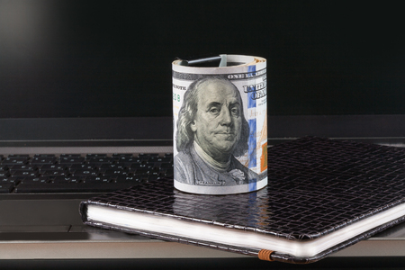 Laptop and notebook,dollars banknote, concept and idea of time value and money, realestate business and finance concepts. retro, green with the hands