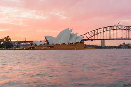 nsw: Sydney Opera House and Harbour Bridge at sunset. Sep,11,2016.The Sydney Opera House,Sydney,NSW,Australia.It was designed by Danish architect Jorn Utzon, finally opening in 1973.