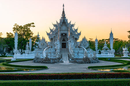 Wat Rong Khun(White temple)at sunset in Chiang Rai,Thailand.23012018 Wat Rong Khun is modern building, well known worldwide.It was designed by Chalermchai Kositpipat.Opened it to visitors in 1997.