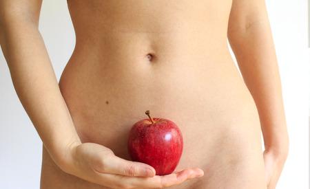 abdomen plano: Mujer joven que sostiene una manzana contra su cuerpo Foto de archivo