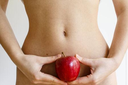 flat stomach: Giovane donna che tiene una mela rossa contro il suo ventre piatto Archivio Fotografico