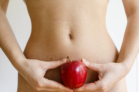 Young woman holding a red apple against her flat stomach photo