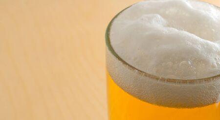 spume: Pub spume, atop glass, close-up.