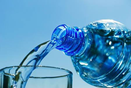 Mineral water, pouring from bottle in glass, close-up. photo