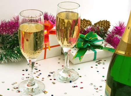 sweetmeats: Two goblets champaign, close-up, tinsel, sweetmeats, bottle, bolls, on light background and the other attributes new year and cristmas.