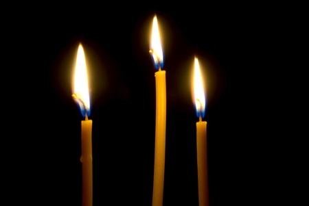 plea: Three burning, church, waxy candles, close-up illuminate the darkness, before itself.