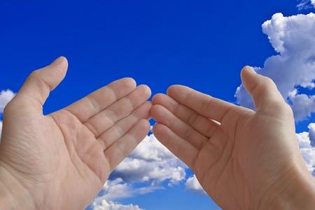 2 手のひら、祈り、用に構築された背景の青い空と雲のクローズ アップ。
