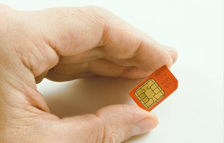Sim card, red colour, numbered, deducted, finger of the hand, white men, on light background. photo