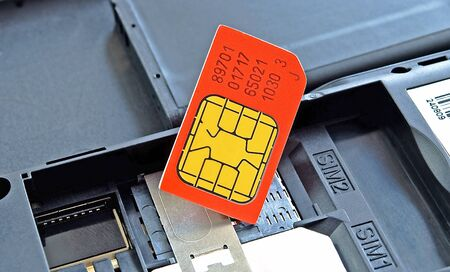 Simkaart rode kleur, close-up, op de achtergrond van de mobiele telefoon.