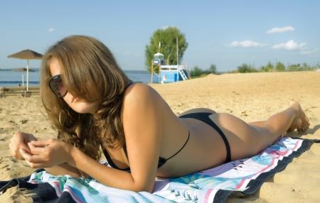 Girl in bikini tans on beach. photo