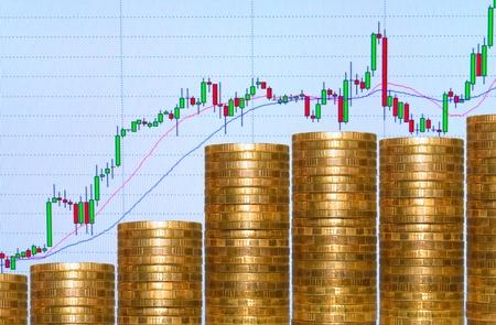 Grafiek van munten, op de achtergrond afbeeldingen op de monitor.