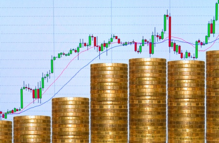 Graph from coins, on background graphics on monitor. Stok Fotoğraf