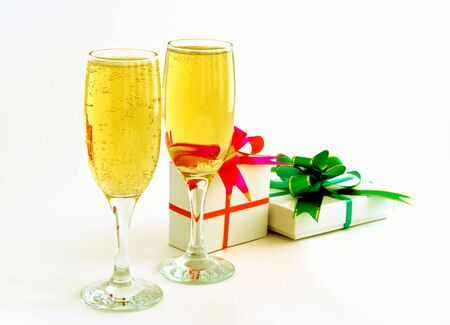Two full goblets champaign, close-up, on light background, and two �������� executed as gift, with ���������� red and green colour, and bow. photo