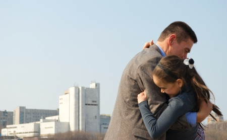 Joyful father hugs his daughter, against the backdrop of the city.