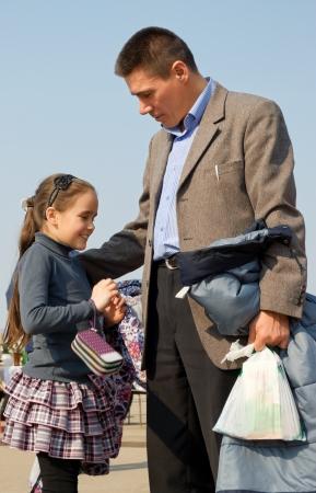 edificación: Padre e hija caminando en la primavera de la ciudad.