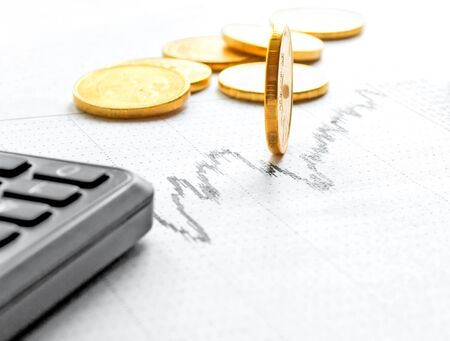 Coins from the yellow shiny metal calculator on paper chart. Stock Photo - 15531749