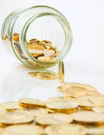 黄色金属の硬貨は、瓶からこぼれます。 写真素材