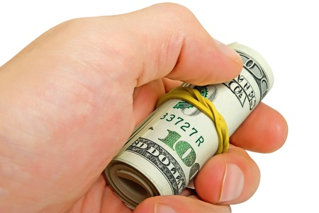 concealment: Roll of dollars in a mans hand, close-up.