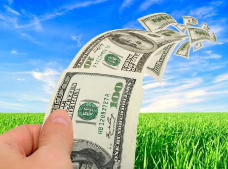 Stroom van geld in de hand tegen de hemel en gras