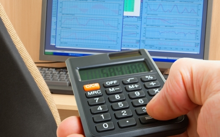 speculating: Calculator in hand on a background of the monitor, a table and chairs.
