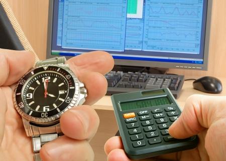 Klok en rekenmachine in de hand op de achtergrond van de monitor om het schema op de tafel en stoelen.
