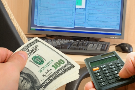 Pack of dollars and calculator in hand on a background of the monitor on the desk and chair. Stock Photo - 18629516