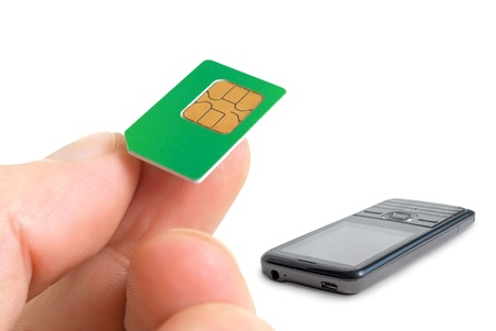 Sim card in a mans hand and mobile phone.