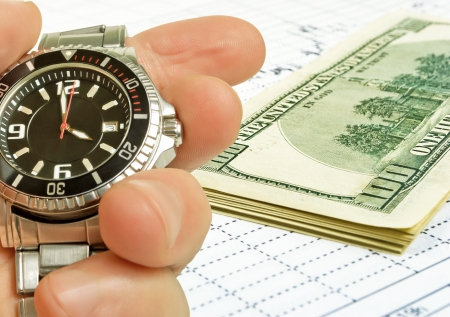 The hand with the clock on the background of the exchange graph with a pack of dollars. Stok Fotoğraf