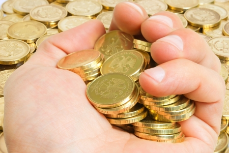extortion: Hand with coins on background of coins on the plane  Stock Photo