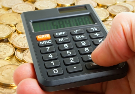 subsidy: A hand with a calculator on the background of coins on the plane