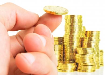 Een hand met een muntstuk op zijn vinger, een stapel munten op een witte achtergrond Stockfoto