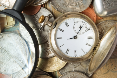 Still life with pocket watches, coins and magnifying glass