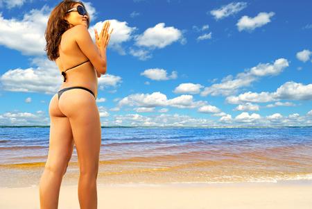 Sexy girl in a bikini on a sunny beach  photo