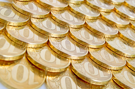 Shiny, yellow coins orderly arranged on the plane  Stock Photo