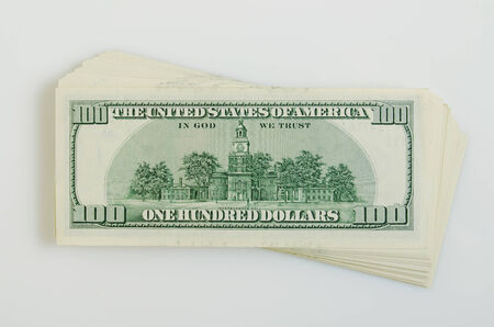 transfers: A stack of US dollars on a white plane.